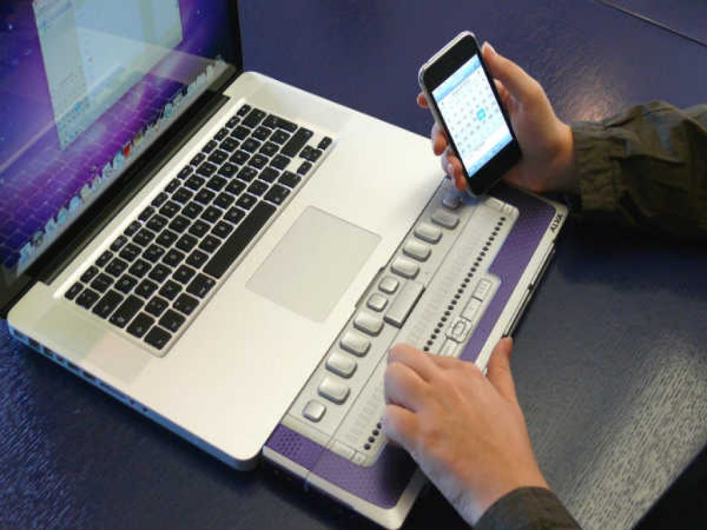 A visually impaired person using the braille display to access the web
